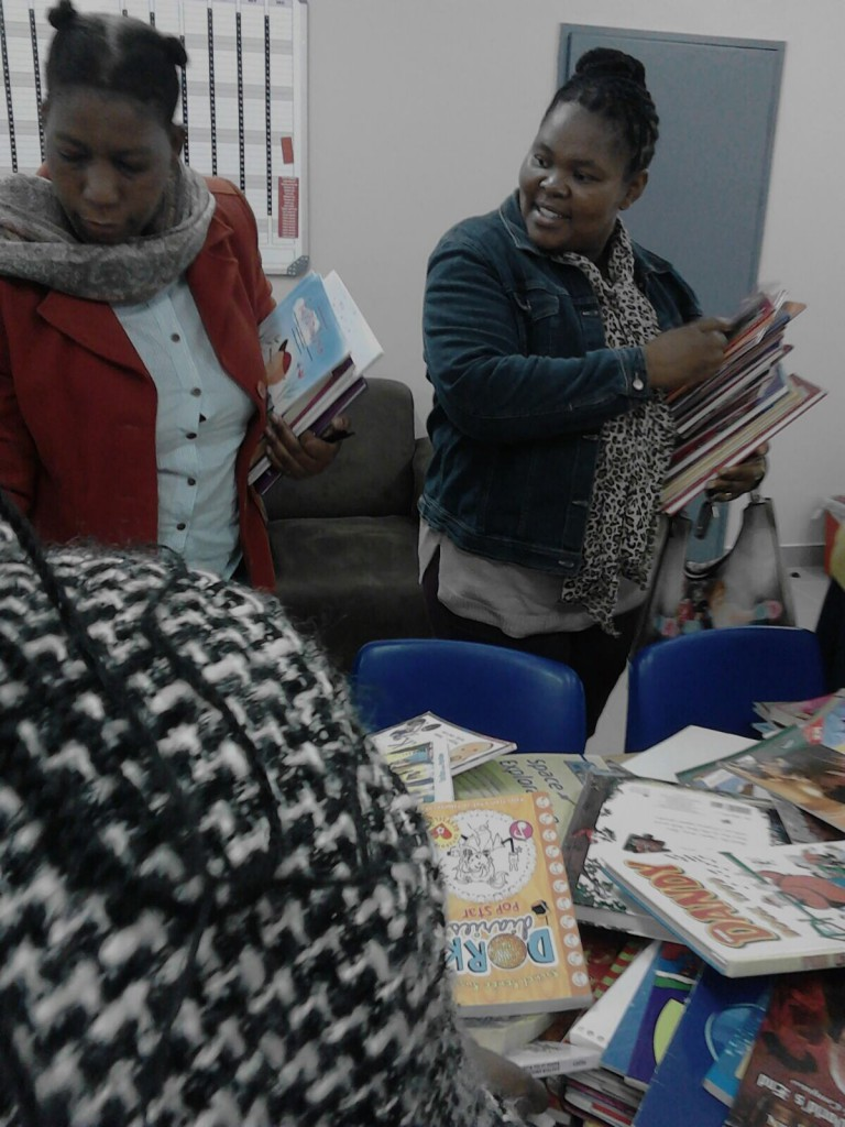 Teachers selecting books from book collection 2